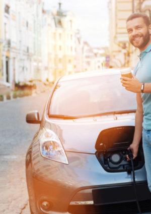 Homme souriant avec café en chargeant sa voiture électrique