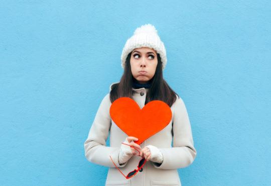 Fille exaspérée tenant un coeur, n'aime pas la saint-valentin