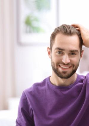 homme se touchant les cheveux souriant