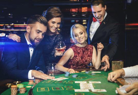 Groupe de 4 jeunes hommes et femmes séduisants jouant des jeux d'argent dans un casino