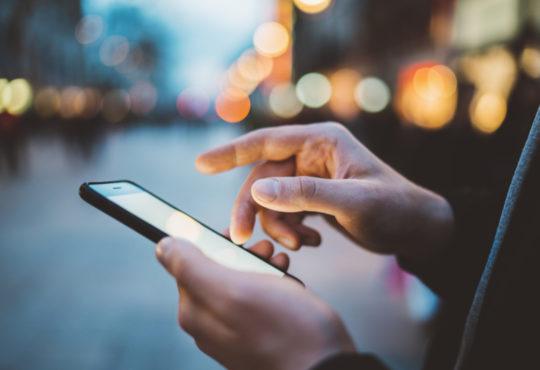 Homme tapant sur un smartphone dans les rues d'une ville la nuit