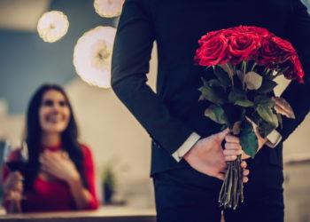 Homme tenant des fleurs dans son dos devant femme heureuse du geste