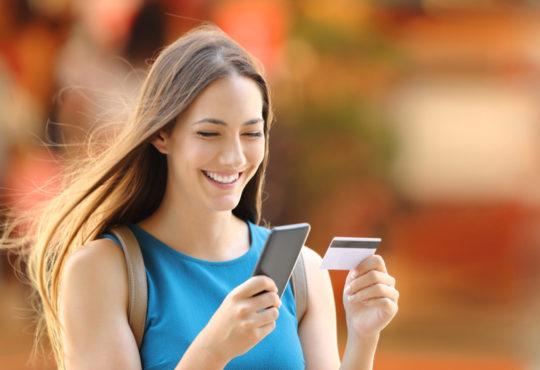 Jolie femme souriante tenant une carte bancaire et un smartphone heureuse