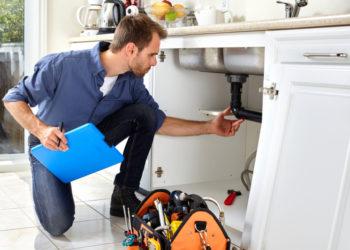 Un plombier près d'un évier pour évaluer les dégâts d'une intervention d'urgence
