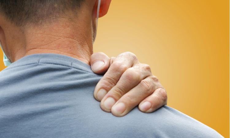Un homme se masse l'épaule pour se soulager de la douleur